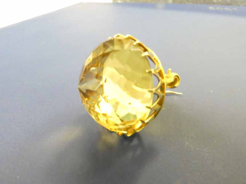 A yellow metal Brooch, set with a large circular domed Citrine, multi facetted in a spiral effect,