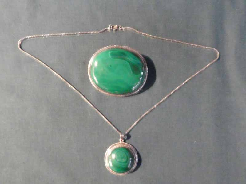 A large pin Brooch, oval form with Malachite set into a white metal mount with gadrooned edge, 6.5cm