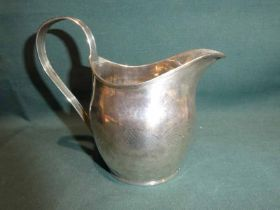 A George III early 19th century silver Creamer, oval form reeded strapwork handle and rim,