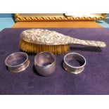 A silver backed Dressing Table Brush with embossed decoration, a pair of silver napkin rings with