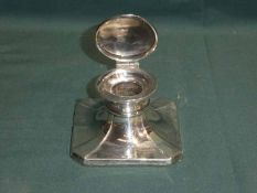 A mid century silver Capstan Ink Well, square canted form, hinged circular cover, glass well not
