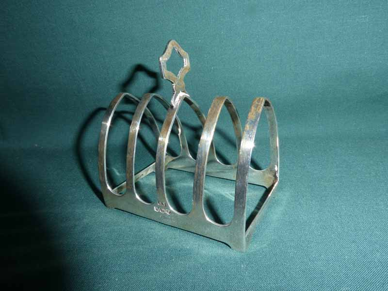 A mid century silver Four Slice Toast Rack, lancet shape with central carry handle, Sheffield