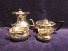 An Edwardian silver Four Piece Tea Service, rounded rectangular form with gadrooned body, embossed