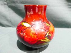A Moorcroft pottery Vase of squat form, tubeline decorated with Orchids on a brown/blue ground, 13cm
