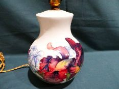 A Moorcroft pottery Table Lamp Base, tubeline decorated with Summer blooms on a cream ground, 20cm