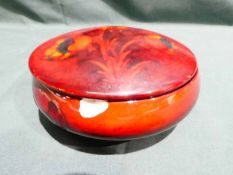 A Walter Moorcroft pottery lidded box of squat circular form, tubeline decorated in Solifleur design