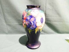 A Walter Moorcroft pottery Vase of baluster form, tubeline decorated with Anenomes on a deep blue
