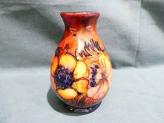 A small Walter Moorcroft pottery Vase of ovoid narrow neck form, tubeline decorated with Anemones on