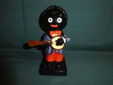 A Carlton Ware hand painted Golly Figure, left handed Banjo Player, colour trial piece, 21cm high