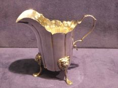 A good quality Edwardian silver Cream Jug, helmet shape with S scroll handle, standing on three