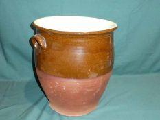 A terracotta twin handle Crock, brown glazed upper portion, 38cm high