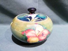 A Walter Moorcroft pottery lidded Jar of squat circular form, tubeline decorated with Fuchsia on a