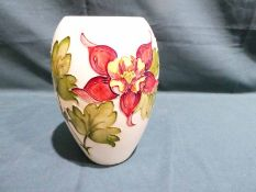 A Moorcroft pottery Vase of ovoid form, tubeline decorated with Hibiscus on a cream ground, 18cm