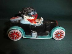 A Carlton Ware hand painted Golly Figure, Driving a Car, trial colourway, 12cm long
