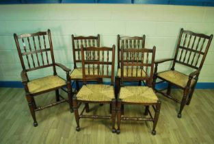 A set of six stained beech rush seat Yorkshire dining chairs on turned legs to pad feet
