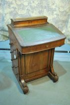 A Victorian walnut Davenport desk with elevated stationary compartment and maple lined well, on four