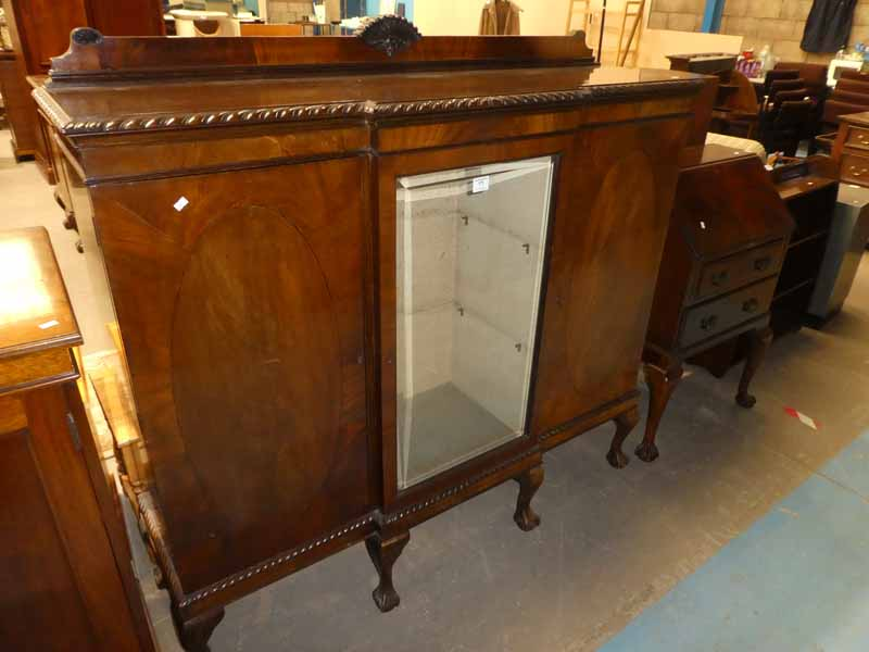A 1930's mahogany display cabinet with glazed central door flanked by enclosed cabinets on short