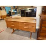 A 1970's teak dressing table with four drawers and framed rectangular mirror, vertical crack to