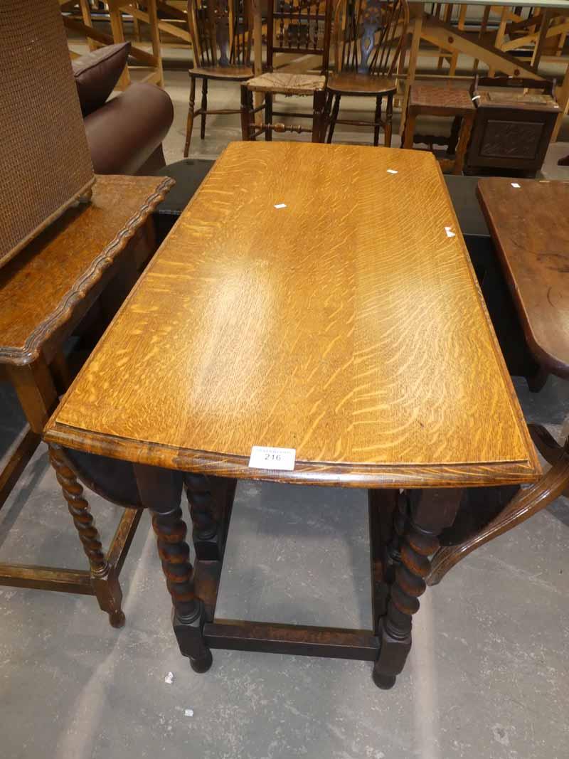 An early 20th century oak oval drop leaf dining table on twist gateleg base