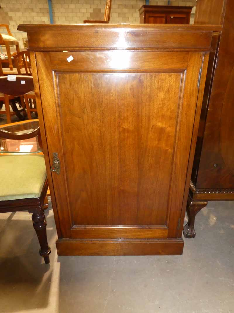 A freestanding mahogany cabinet with single door enclosing a shelved interior
