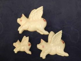 A graduated set of three pottery flying pigs
