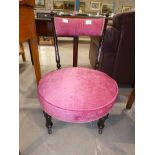 A late Victorian/Edwardian ebonised Nursing chair with pink upholstered circular seat and bar