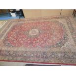 A large middle eastern style carpet, central medalion within red foliate panel and multiple
