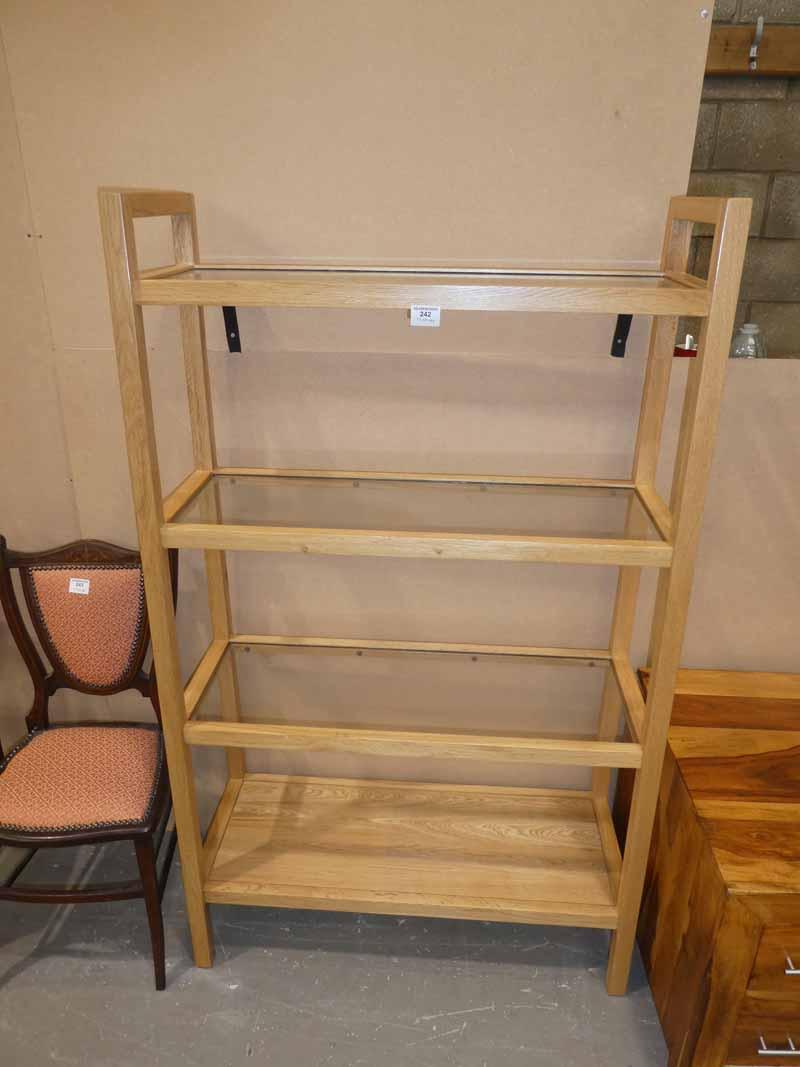 A light oak four tier bookcase with glass shelf inserts