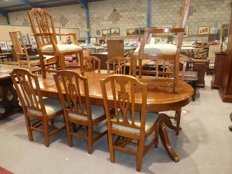 A modern Walnut effect twin pillar D ended extending Dining table with spare leaf and a set of