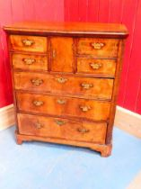 A George II walnut bachelors chest, the central pigeonhole cupboard is flanked by four small drawers