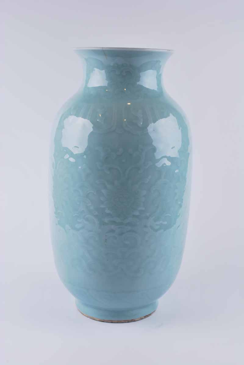 A Chinese celadon glazed vase, baluster form with everted neck decorated in low relief with lotus
