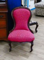 Victorian mahogany spoon back nursing chair on scroll legs and finished in claret brocade 88cm H