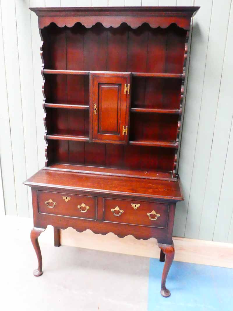 A George III oak dresser , the plate rack with central cupboard surmounts the two drawer base on