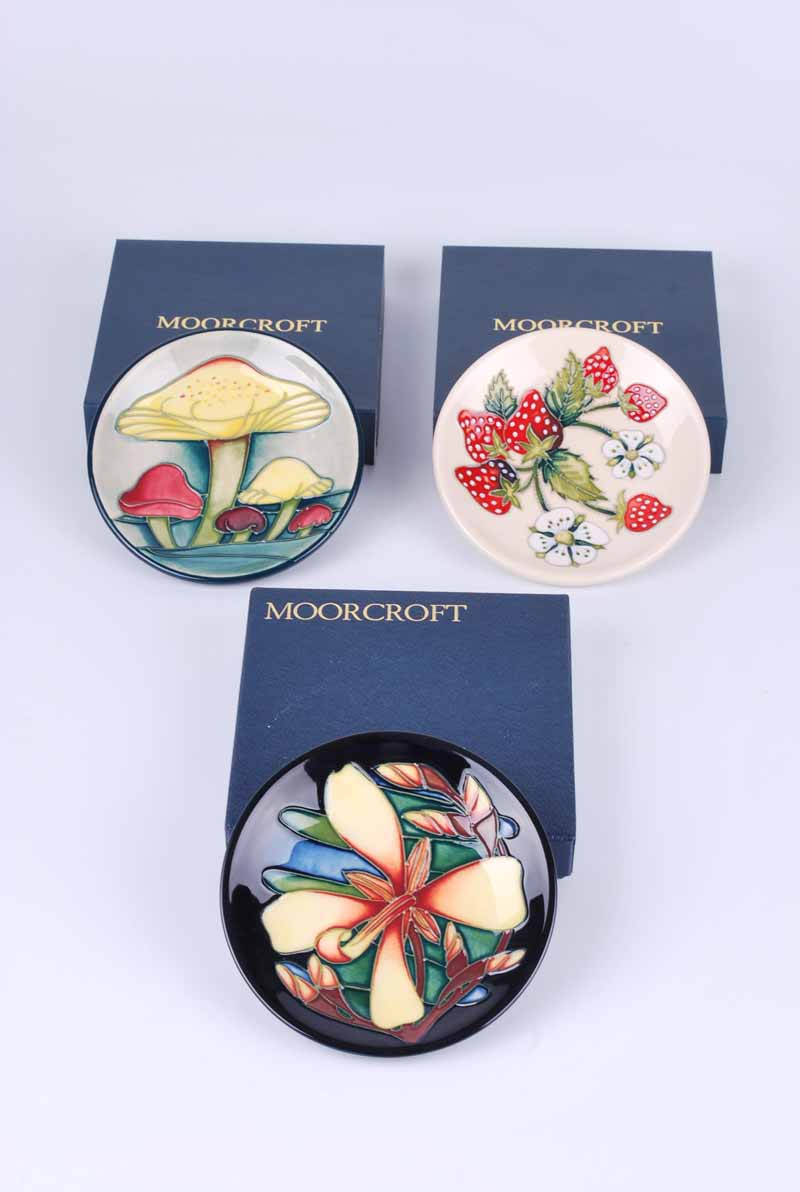 Three Moorcroft pin dishes, one decorated with fungi, one with strawberries, and the other in the