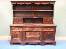 A George III and later oak dresser, the later plate rack with twin cupboards to each side