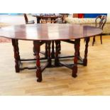 A good quality reproduction 18th century style oak wake table, hinged oval top with a pair of drop