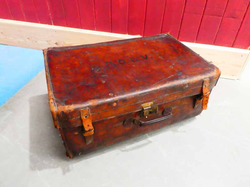 An early 20th Century large leather suitcase marked ODBV to the lid and remnants of steamer labels