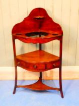 An early 19th Century mahogany corner wash stand of typical form with shaped back wells suitable for