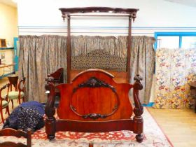 A Victorian mahogany half tester bed; the serpentine footboard with applied cartouche and flanked by
