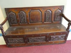 George II oak settle with berry carved panel back embellished with rosettes and early strap hinges