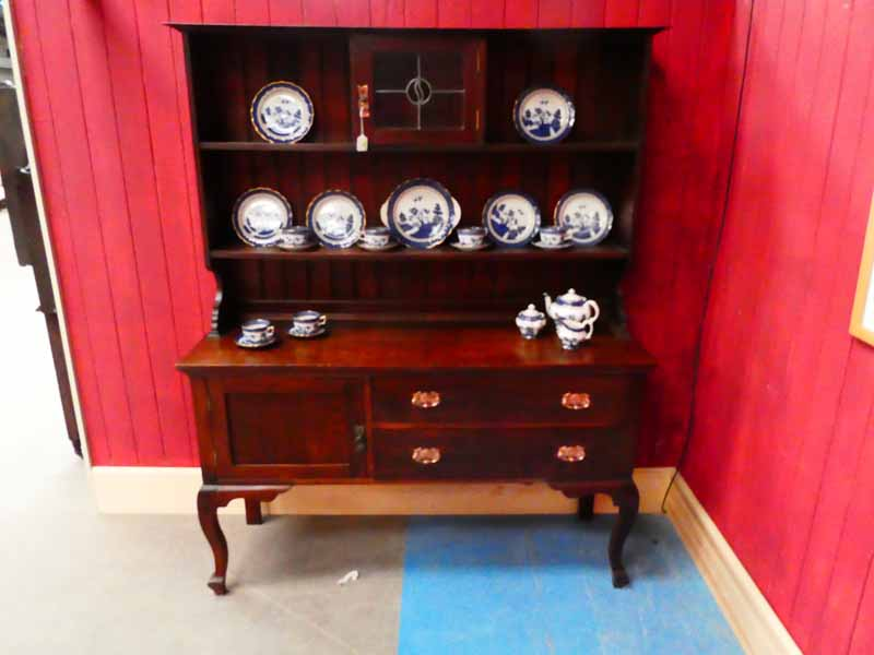An oak Craft Dresser, the shallow rectangular moulded cornice above a shelved boarded display back