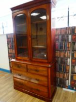 A Victorian flame mahogany two door glazed bookcase on chest of four drawers with square aesthetic
