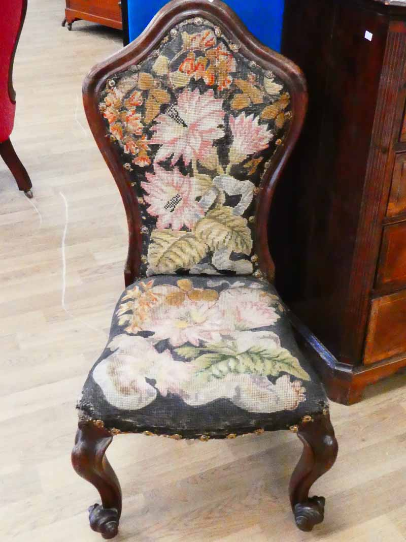 A Victorian nursing chair in rosewood with tapestry cover