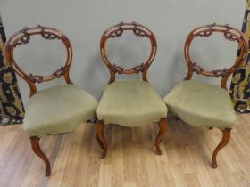 3 Victorian walnut open backed balloon chairs with stylised acanthus leaf decoration over stuffed