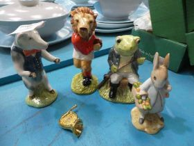Four Beswick pottery models: Pig Prom, Last Lion, Fly Fishing and Peter Rabbit gardening.