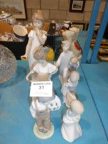 A collection of six Lladro and Nao figure groups of children