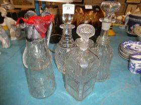 A collection of four glass decanters and a claret jug
