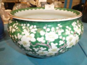 A mid 20th century green ground Chinese porcelain planter in prunus to green ground