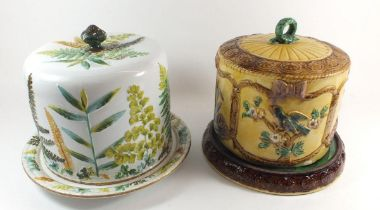 Two Victorian Majolica cheese domes, one marked Adderley with fern design and the other with flowers