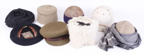 Two embroidered Indian skull caps and one other; Afhgan goat skin cap; British army field cap;